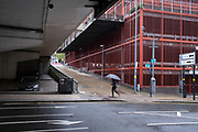 Man with an umbrella passes the red cage town hall car park in Birmingham city centre, which is virtually deserted under Coronavirus lockdown on a wet rainy afternoon on 28th April 2020 in Birmingham, England, United Kingdom. Britains second city has been in a state of redevelopment for some years now, but with many outdated architectural remnants still remaining, on a grey day, the urban landscape appears as if frozen in time. Coronavirus or Covid-19 is a new respiratory illness that has not previously been seen in humans. While much or Europe has been placed into lockdown, the UK government has put in place more stringent rules as part of their long term strategy, and in particular social distancing.