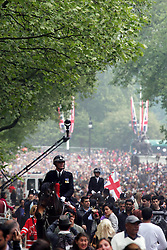 29 April 2011. London, England..Royal wedding day. Huge crowds swell the streets and promenades leaving Buckingham Palace as the Royal family retreats inside for the afternoon activities. .Photo; Charlie Varley.