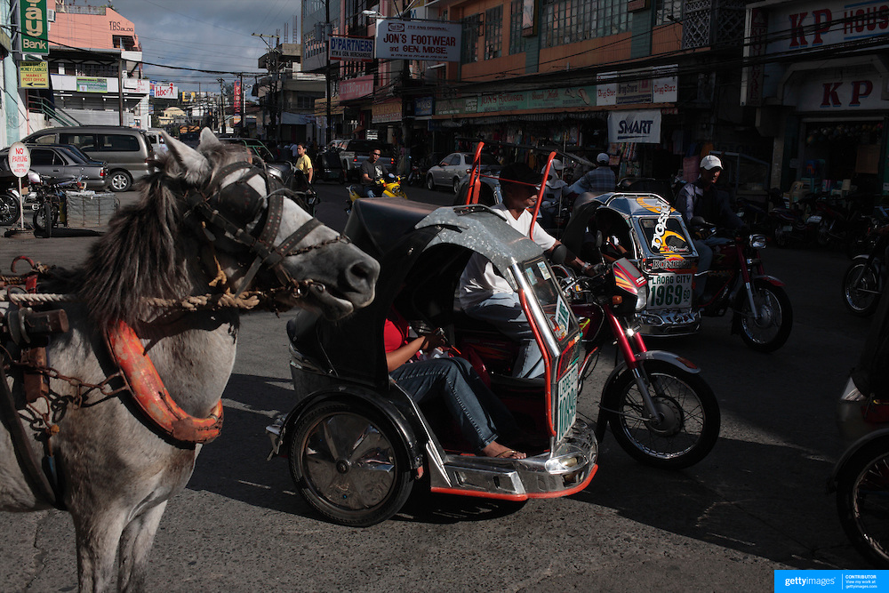 A Street Scene in Laoag City, Ilocos Norte, the Philippines on September 26, 2008 as motorized tricycles are used as taxi's while horse drawn transport is still evident. Photo Tim Clayton