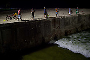 Brazilian men cariocas fishing for the few fish that come into this potentially polluted channel, coming from the beach near Ipanema, Rio de Janeiro. In this smart neighbourhood there is a large gap between rich and poor, with people having to catch fish for their food. Night time.