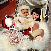 Europe, Scandinavia, Finland, Porvoo. Dolls bundled up in a baby carriage parked outside a shop in Porvoo in summertime - a reminder of the undeniable winter in Finland.