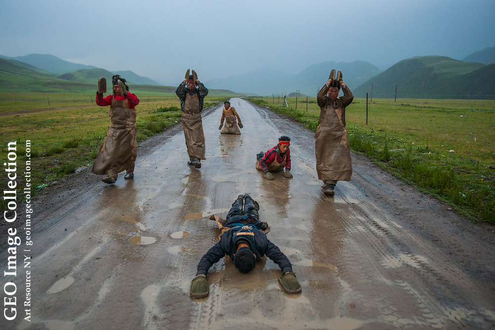 On the Road to Lhasa and the Top of the World: Devout pilgrims proceed at a snail's pace performing the chak tsal, the Tibetan name for ritual prostration. Their journey from Qinghai will take six months, along the northern branch of the Tea Horse Road to the sacred city of Lhasa. Tibet