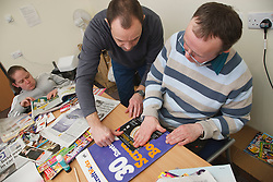Client with Downs Syndrome being helped by carer doing craft activity at a resource for people with physical and sensory impairment.