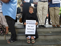 Wednesday 2nd October 2016.<br /> St. George's Cathedral,<br /> Cape Town,<br /> Western Cape,<br /> South Africa.<br /> <br /> #SaveSouthAfrica Silent Prayer Vigil In Cape Town!<br /> <br /> A Religious Leader sits holding a placard that reads 'A lament for our beloved country' as she and other Concerned Citizens and Religious Leaders stand together in silent protest on the steps of St. George's Cathedral in Cape Town.<br /> <br /> Concerned Religious Leaders and other South Africans gathered together in silent protest in support of the call to #SaveSouthAfrica from 'the acute social crisis that has been brought about by corruption, mismanagement and political intrigue' as reported nationwide in the news. The campaign was formed under the banner of holding government leaders accountable to the Constitution and the values they have pledged to uphold as representatives of the people. The #SaveSouthAfrica Silent Prayer vigil was held at St. George's Cathedral in Cape Town, South Africa on Wednesday 2nd November 2016.<br /> <br /> Picture By:  Mark Wessels / RealTime Images.