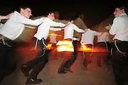 Israel, Haifa, Neve Shaanan, Jews dance around the bonfire during the lag b'omer celebrations. Lag B'Omer is a day for bonfire celebrations.