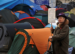 © Licensed to London News Pictures. 17/11/2011, London, UK. A woman holds a banner at Occupy London tents outside St Paul's Cathedral today 17 November 2011.  Photo credit : Stephen Simpson/LNP