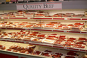 A display of red meat fills the shelves of a generic supermarket store in London. A sign tells us the beef has quality - its packaging is all the same size making each steak or joint a uniform size and shape.