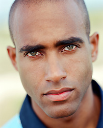 portrait of a handsome African American man with beautiful green eyes outdoors