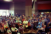 New arrivals, wet from the rain, gather in the bar for instructions at Butlins Holiday camp in Skegness. Butlins Skegness is a holiday camp located in Ingoldmells near Skegness in Lincolnshire. Sir William Butlin conceived of its creation based on his experiences at a Canadian summer camp in his youth and by observation of the actions of other holiday accommodation providers, both in seaside resort lodging houses and in earlier smaller holiday campsThe camp began opened in 1936, when it quickly proved to be a success with a need for expansion. The camp included dining and recreation facilities, such as dance halls and sports fields. Over the past 75 years the camp has seen continuous use and development, in the mid-1980s and again in the late 1990s being subject to substantial investment and redevelopment. In the late 1990s the site was re-branded as a holiday resort, and remains open today as one of three remaining Butlins resorts.