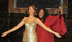 "© Licensed to London News Pictures. 21 October 2013. London, England. Pictured: gospel singer Simone Daley-Richards poses with the figure. The 30-strong ""London Gospel Factory Choir"" today welcomed the wax figure of singer Whitney Houston at Madame Tussauds London, where it will be on display until the middle of December 2013. Photo credit: Bettina Strenske/LNP"