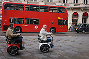 Two men ride on a couple of Segway-powered GennyMobility wheelchairs in Leicester Square, central London.