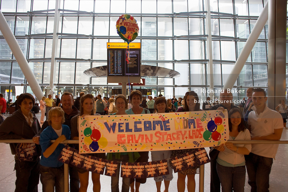 A family awaitng loved-ones in Arrivals of Heathrow's terminal 5 stretch a banner and float a helium-filled balloon.
