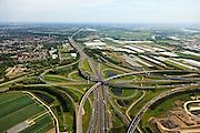 Nederland, Zuid-Holland, Ridderkerk, 23-05-2011; Knooppunt Ridderkerk, verkeersknooppunt A15 / A16, bijgenaamd 'Ridderster'. Gezien naar het zuiden, richting Breda met rechts bedrijventerein Nieuw Reijerwaard. Klaverblad met opritten, afritten en fly-overs. De waterpartijen zijn kunstmatige aangelegd en kunnen dienen als bluswater ingeval calamiteiten..Ridderkerk junction, junction A15 / A16, nicknamed 'Ridder star'.  Cloverleaf type junction, with ramps, exit ramps and flyovers. The ponds are man-made and the water can be used for  firefighting in case of emergencies..luchtfoto (toeslag), aerial photo (additional fee required).copyright foto/photo Siebe Swart