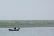Fisherman in small dory boat in the rain and fog on Big Lagoon, Humboldt Lagoons State Park, California