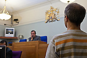 In a magistrates court in England, models pose as defendant and Judge.