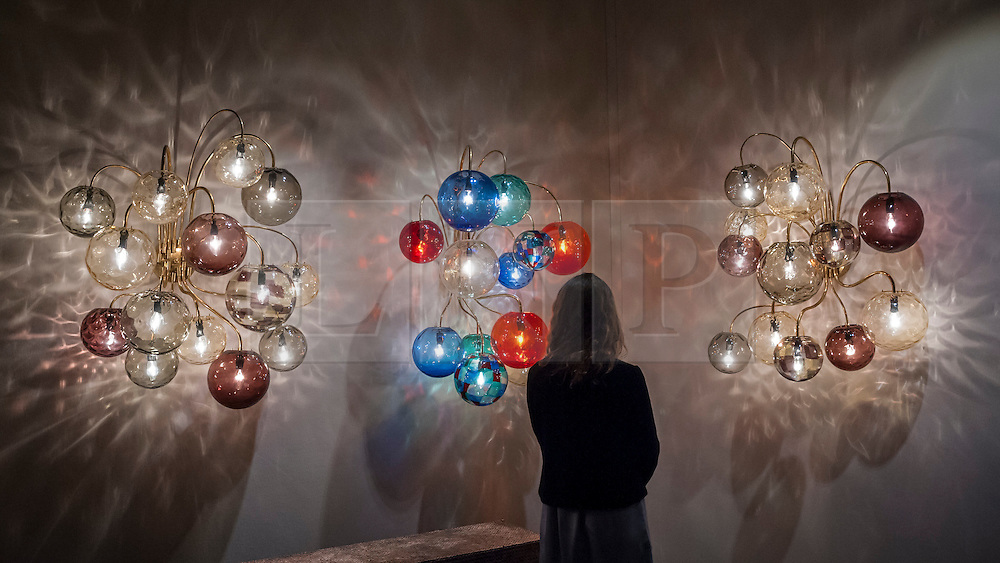 © Licensed to London News Pictures. 24/06/2015. London, UK.   A visitor views a set of ornate Italian lights, at the preview of Masterpiece London, the international cross-collecting Fair for art, antiques and design which takes place at The Royal Hospital Chelsea 25 June to 1 July. Photo credit : Stephen Chung/LNP