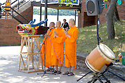 Monks blessing festival and snout of dragon from racing boat. Dragon Festival Lake Phalen Park St Paul Minnesota USA