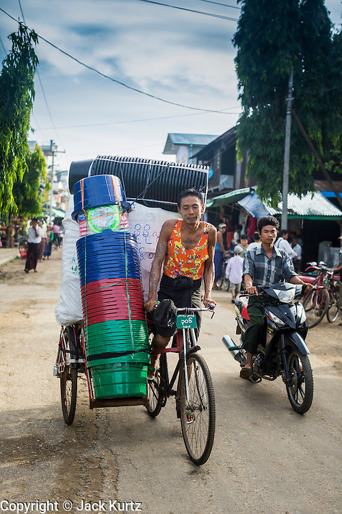 06 JUNE 2014 - IRRAWADDY DELTA,  AYEYARWADY REGION, MYANMAR: A man on a pedicab brings plastic tubs to the market in Pantanaw, a town in the Irrawaddy Delta (or Ayeyarwady Delta) in Myanmar. The region is Myanmar's largest rice producer, so its infrastructure of road transportation has been greatly developed during the 1990s and 2000s. Two thirds of the total arable land is under rice cultivation with a yield of about 2,000-2,500 kg per hectare. FIshing and aquaculture are also important economically. Because of the number of rivers and canals that crisscross the Delta, steamship service is widely available.   PHOTO BY JACK KURTZ