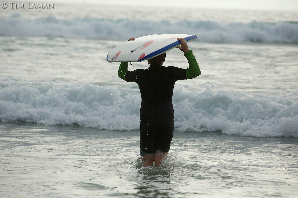 A 12 year-old boy with a boogie board in the ocean.