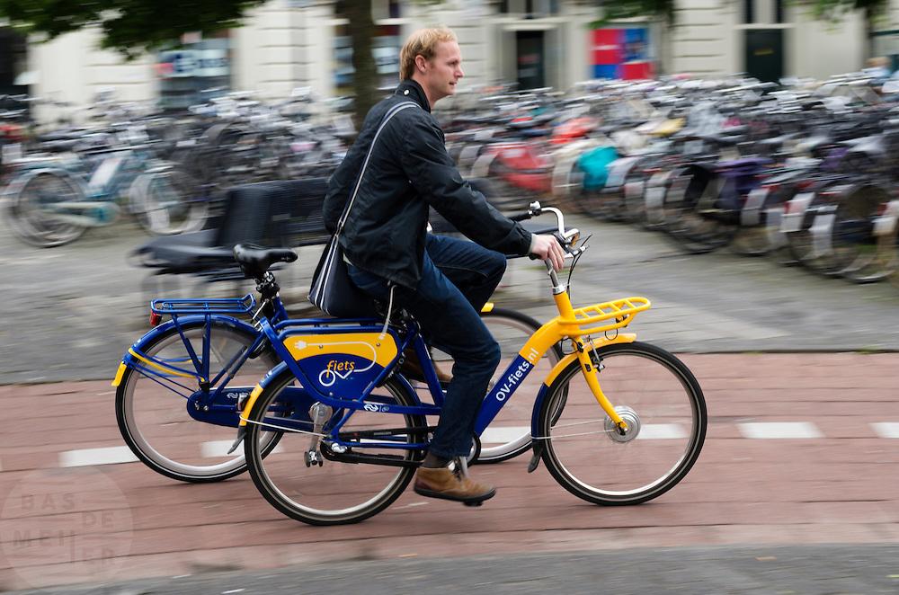 In Leeuwarden fiets een man op een elektrische OV-fiets met een andere OV-fiets aan de hand.<br /> <br /> In Leeuwarden a man is cycling on an electrical OV-fiets, with another OV-fiets in his hand.