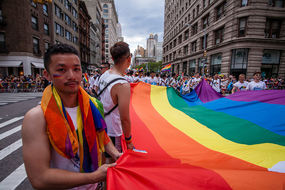 New York, NY - 25 June 2017. New York City Heritage of Pride March filled Fifth Avenue for hours with groups from the LGBT community and it's supporters. Marchers from the China Rainbow Network with a huge rainbow banner.