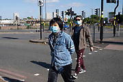 People wearing face masks crossing Bristol Street in the inner city area of Birmingham virtually deserted under Coronavirus lockdown on 5th May 2020 in Birmingham, England, United Kingdom. Coronavirus or Covid-19 is a new respiratory illness that has not previously been seen in humans. While much or Europe has been placed into lockdown, the UK government has put in place more stringent rules as part of their long term strategy, and in particular social distancing.