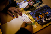 """A young Roma girl is getting help with her homework at the The Salesians of Don Bosco Pastoral Mission at Lunik IX, she is writing about a fairy tale named  """"the beautiful gypsy"""" (krasna ciganka)."""