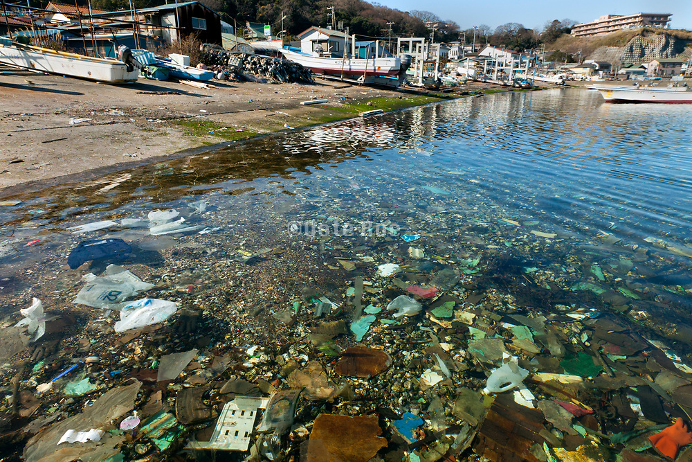 small fishers boat port with various plastic trash in the water Yokosuka Japan