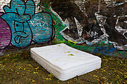 An abandoned mattress on the ground among Autumn leaves on the Regents Canal in Hackney, on 16th October 2018, in London, England.