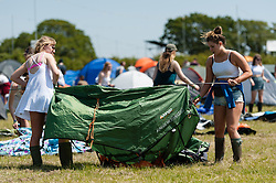 © Licensed to London News Pictures. 11/06/2015. Newport, UK.  Festival goers pitch their tents at the Isle of Wight Festival 2015 in the warm sun accompanied by a strong breeze, just after being allowed onto the campsite at midday. This years festival include headline artists the Prodigy, Blur and Fleetwood Mac.  Photo credit : Richard Isaac/LNP