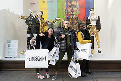 © Licensed to London News Pictures. 08/11/2018. London, UK. Customers leave the HM store in Oxford Circus with shopping bags of items from the Jeremy Scott H&M X Moschino collection. Photo credit: Ray Tang/LNP