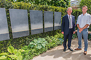 Matthew Keightley (r) and Owen Paterson, Minister for Agriculture, on the Hope on the Horizon garden.  The<br /> 'Hope on the Horizon' garden in aid of Help for Heroes: produced by building and landscaping firm Farr and Roberts', making their debut; designed by Matthew Keightley (29), as a result of his brother Michael's involvement with the armed forces, having served on four tours to Afghanistan and due for his fifth this year; and sponsored by the David Brownlow charitable foundation. The garden layout is based on the shape of the Military Cross, the medal awarded for extreme bravery. Granite blocks will represent the soldiers' physical wellbeing and the planting represents their psychological wellbeing at various stages of their rehabilitation. Both evolve through the garden from a rough, unfinished, over-grown beginning through to a perfectly sawn, structured end. An avenue of hornbeams draws the attention through the entire garden to a sculpture resembling a hopeful horizon; a reminder to the soldiers that they all have a bright future ahead. As well as areas to recline and reflect, the garden offers focal points all the way through. Cool, calming colours are used throughout, helping to emphasise the fact that it will be a serene, contemplative space. After the Show, the garden will be moved and set within the grounds at Help for Heroes Recovery Centre at Chavasse VC House in Colchester, Essex. The garden will offer a serene, peaceful haven to contemplate and inspire a bright future and to support the challenging journey to recovery. The Chelsea Flower Show 2014. The Royal Hospital, Chelsea, London, UK.  19 May 2014.  Guy Bell, 07771 786236, guy@gbphotos.com