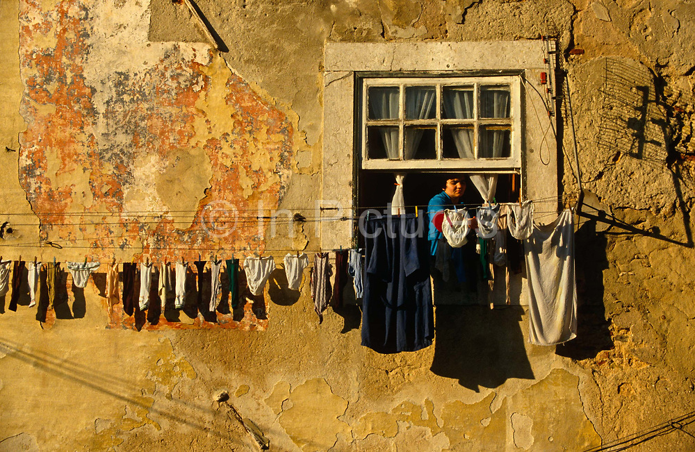 High above the streets of Old Lisbon, we see a Portuguese lady leaning out of her window to hang out her washing on the line that is attached to her home's exterior wall in the Bairro Alto district - or Upper City - the oldest of Lisbon's residential quarters. Items of underwear, socks and other miscellaneous clothing have been strung out on the line that is now pegged along the crumbling wall's surface with faded, peeling plaster and paint. A TV aerial has also been fixed precariously by the window and it's shadow can be seen in the sunshine which is strong and side-lighting the scene which has a warm, morning glow about it. Lisbon's Bairro Alto quarter is located above Baixa and developed in the 16th Century. Suffering very little damage in the earthquake of 1755, it remains the area of most character and renowned for its residential and working quarter for craftsmen and shopkeepers. At night, life takes on a diferent personality when bars and up until the 60s, prostitution gave the district a bad reputation in the past but nowadays tourists and the chic frequent its streets and traditional 'Fado' (classical Portuguese opera) bars.