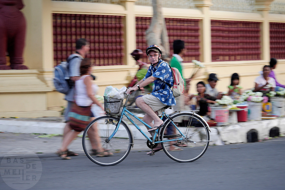 Een westerse man rijdt op de fiets door Phnom Penh