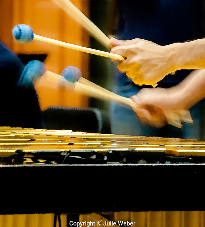 """The vibrant blur of the mallets held by the hands of the musician fills the space between the golden bars of the vibraphone and the player. Golden light reflects from the vibraphone on to the hand of the musician.For IMAGE LICENSING just click on the """"add to cart"""" button above.<br /> <br /> Fine Art archival paper prints for this image as well as canvas, metal and acrylic prints available here:"""