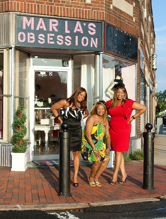 Boston, MA 08/08/2011<br /> Sisters Tricia Adams, wearing a black and white trapless ruffle dress, Marla Adams, wearing a halter paisley dress, and Melissa Adams, wearing a red cap sleeve dress, are co-owners of Marla's Obsession in Roslindale Square.