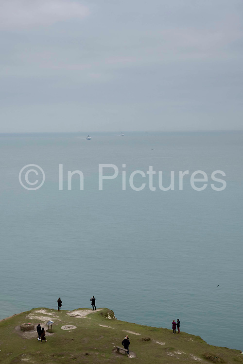 Tourists standing on the edge of the White Cliffs of Dover, Kent. One of the most famous and iconic landmarks of Britain. They face the straights of Dover between England and France. They are part of the North Downs formation and are mostly made up of chalk.