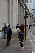 A commuter takes a magazine from between her knees, on 9th February 2017, outside the Bank of England, in the City of London, England.