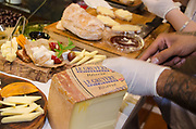 A chef is demonstrating the cutting of cheese at a baking workshop