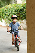 Young boy of six plays outside on his bicycle