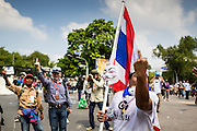 01 DECEMBER 2013 - BANGKOK, THAILAND: Thai anti-government protestors give the middle finger to Thai riot police in Bangkok. Thousands of anti-government Thais confronted riot police at Phanitchayakan Intersection, where Rama V and Phitsanoluk Roads intersect, next to Government House (the office of the Prime Minister). Protestors threw rocks, cherry bombs, small explosives and Molotov cocktails at police who responded with waves of tear gas and chemical dispersal weapons. At least four people were killed at a university in suburban Bangkok when gangs of pro-government and anti-government demonstrators clashed. This is the most serious political violence in Thailand since 2010.    PHOTO BY JACK KURTZ<br /> Flip the bird
