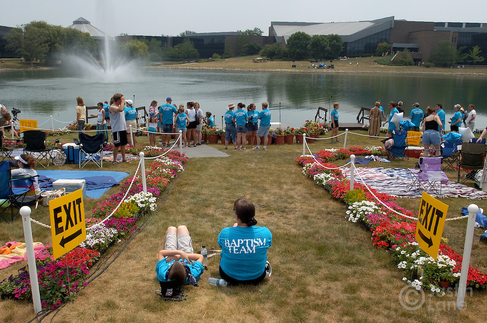 """Two woman wearing t-shirts saying """"Baptism Team"""" are seen before the start of an outdoor baptizing at Willow Creek Community Church, seen in background, in South Barrington, IL on June 26, 2005. The church holds regular mass baptisms at which hundreds of people are baptized in the church's small lake."""