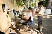 09 MARCH 2006 - HO CHI MINH CITY, VIETNAM: A barber works on a street in Ho Chi Minh City (formerly Saigon) Vietnam. With an unofficial population of nearly 10 million (the official population is 6 million) business is done anywhere a businessperson can find space to do it, including the sidewalk. Photo by Jack Kurtz