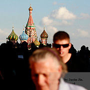People walk through an arch in front of the St. Basil's Cathedral on the Red Square, Moscow.