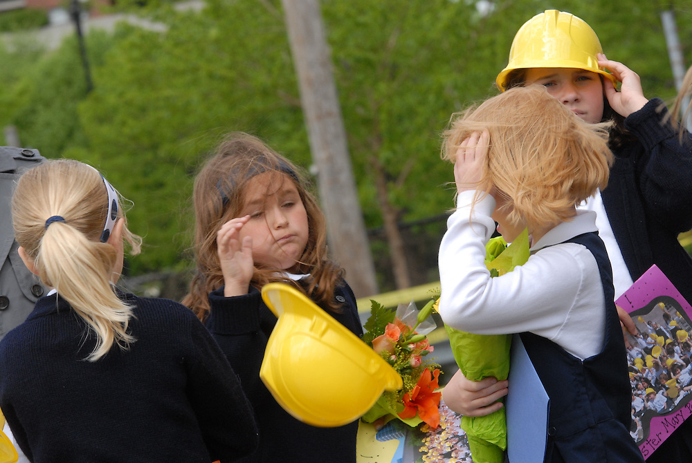 A strong breeze steals a ceremonial plastic hard hat from students attending a ground breaking ceremony at Old St. Mary's Catholic School in Chicago's South Loop neighborhood.