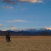Jeff Lyman and Wende Valentine make their way across the Tingri Plains with Everest, Gyachung Kang, and Cho Oyu visible behind; Tibet.