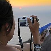 Woman takes a picture of Santorini sunset with postcard in hand