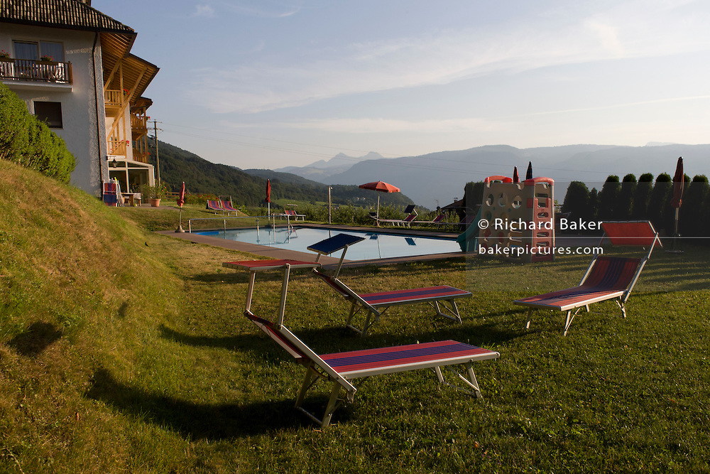 Early morning poolside sun loungers at a country hotel in the Dolomites, rural South Tyrol, south-west of Bolzano, northern Italy.
