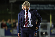 West Ham United manager Manuel Pellegrini looking at the ground during the EFL Carabao Cup 2nd round match between AFC Wimbledon and West Ham United at the Cherry Red Records Stadium, Kingston, England on 28 August 2018.