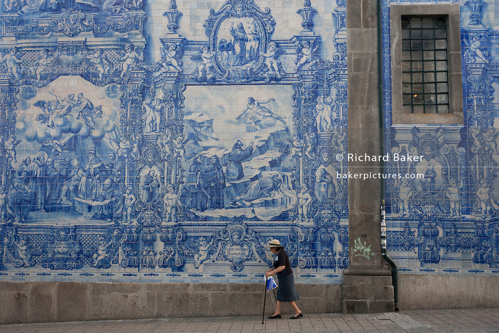 Elderly lady walks with sticks along the Rua de Fernandes Tomas with Azulejo tiles on the exterior of Capela Das Almas, on 20th July, in Porto, Portugal. The Church's magnificent panels depict scenes from the lives of various saints, including the death of St Francis and the martyrdom of St Catherine. Eduardo Leite painted the tiles in a classic 18th-century style, though they actually date back only to the early 20th century. (Photo by Richard Baker / In Pictures via Getty Images)